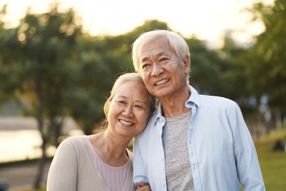 Older couple smiling and holding each other as they're on a walk surrounded by trees and nature.