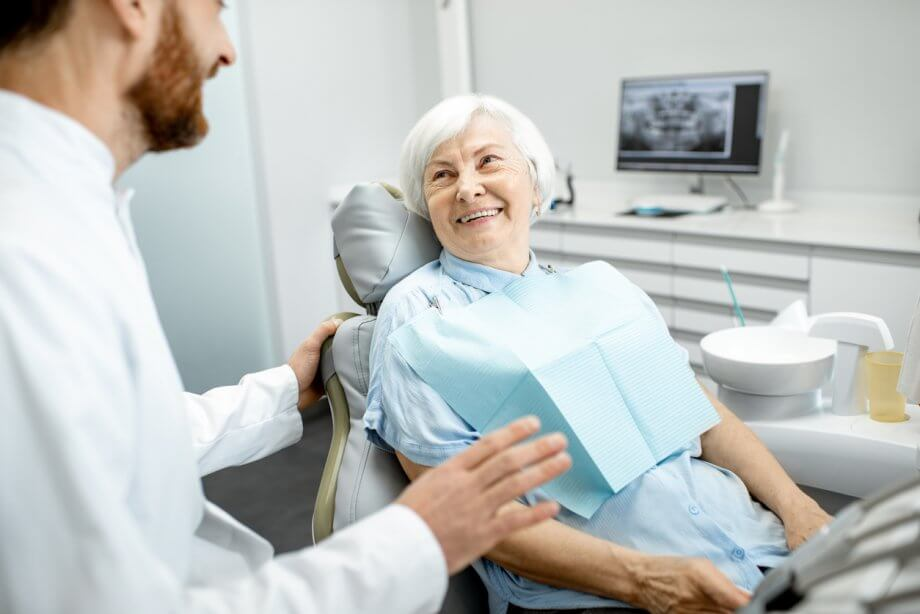 Happy older woman sitting in a dentist chair speaking to the dentist.
