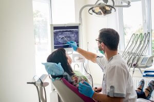 Female patient is being seen by male dentist who is pointing at an x-ray as she looks on.