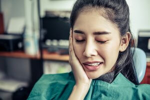 Photograph of a woman holding the right-side of her mouth in pain while in a dentists office.